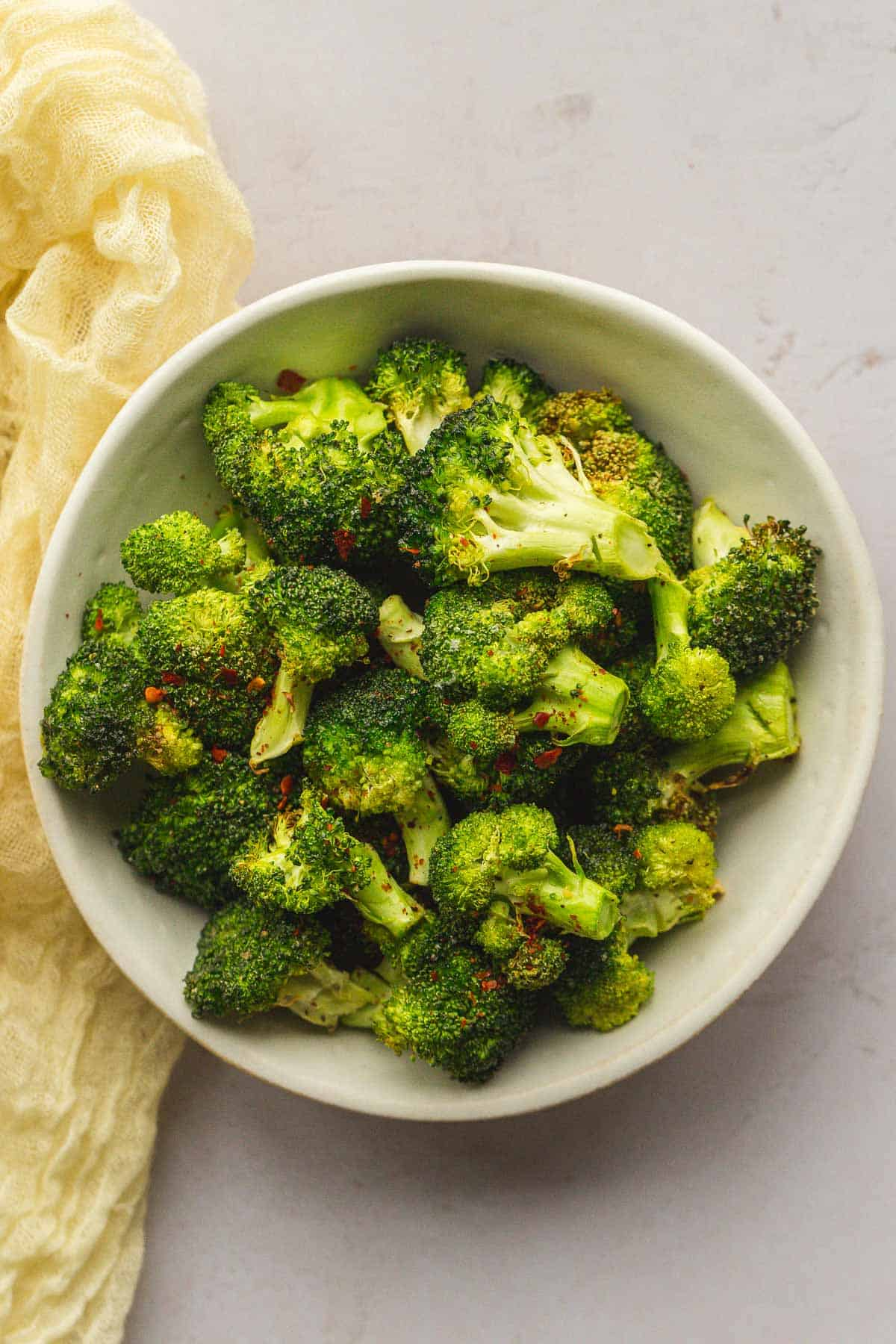 Air Fryer Broccoli in a white bowl, seasoned with chili flakes