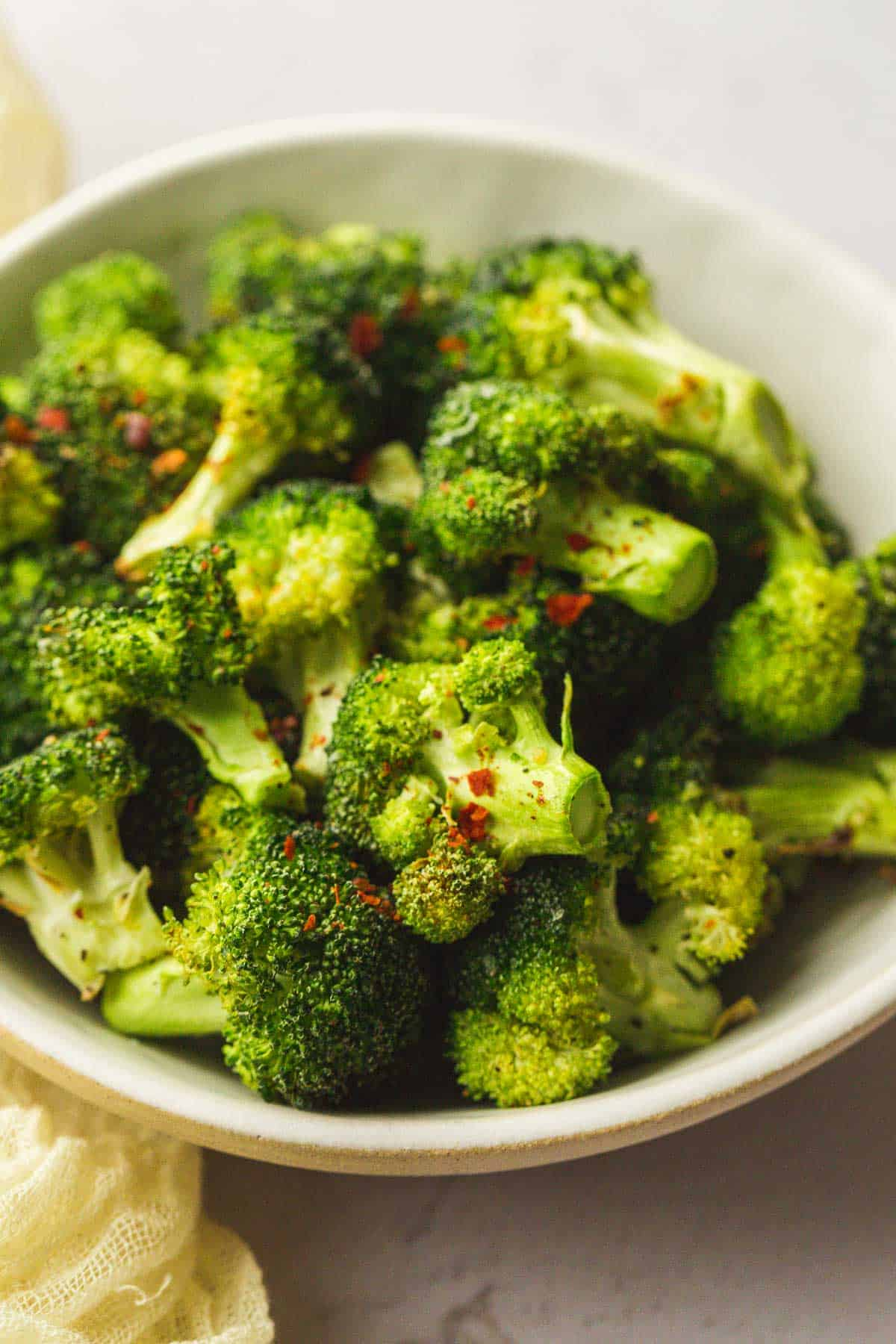 Air fryer broccoli with chilli flakes , served in a white bowl