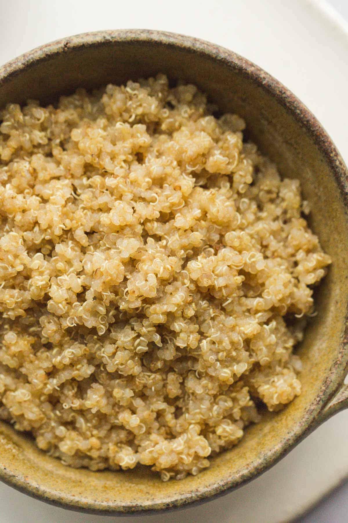 A close up shot of fluffy quinoa in a ceramic bowl