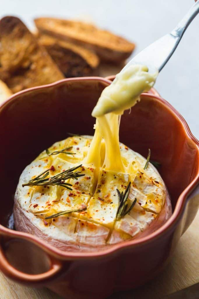 Gooey and melty Baked Camembert cheese in a ceramic baked dish, with rosemary sprigs