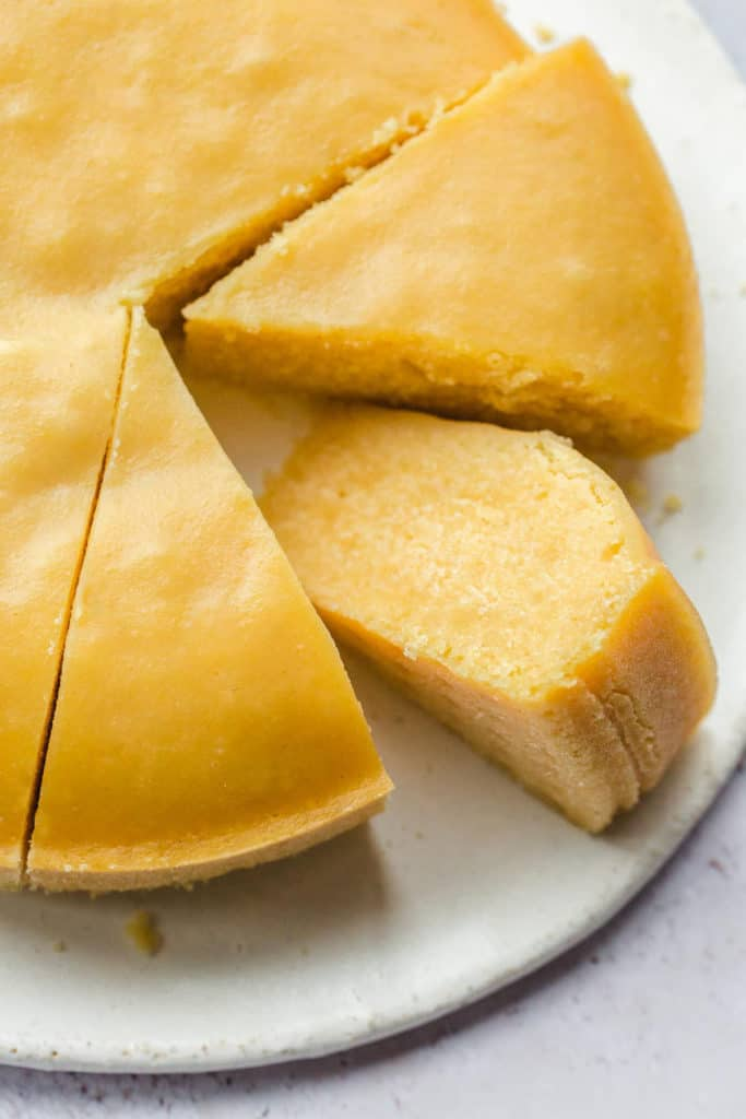 One slice of cornbread on a white plate, and a cornbread round bake