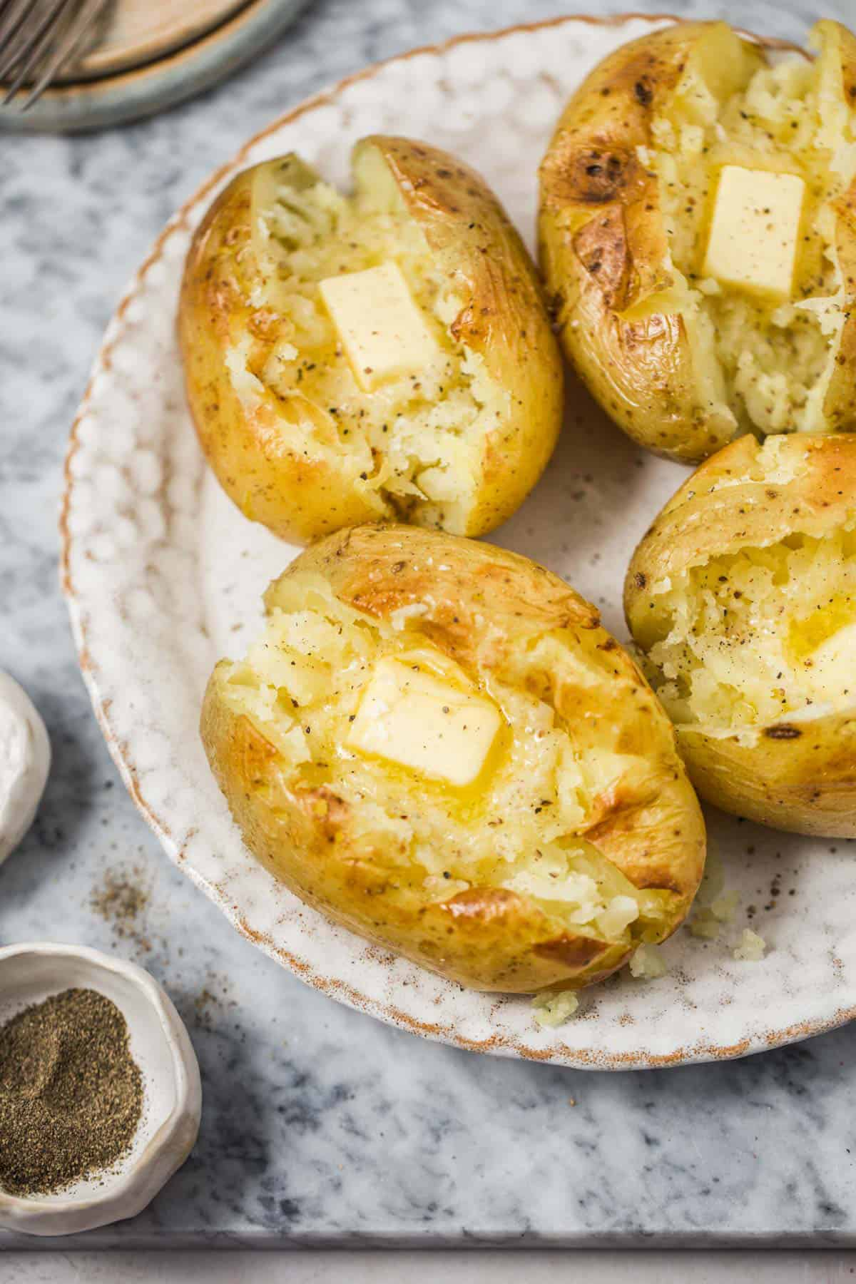 Baked potatoes topped with butter