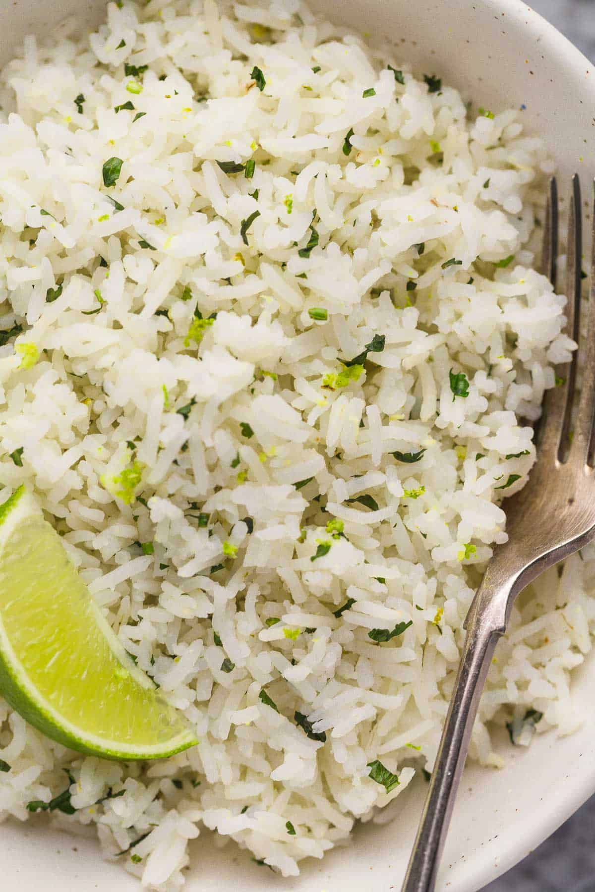 Instant Pot Cilantro Lime Rice in a white bowl with a fork and a wedge of lime