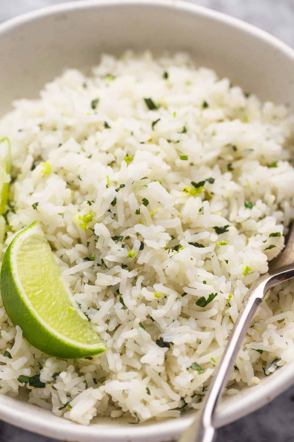 Cilantro Lime Rice served in a bowl with a wedge of lime