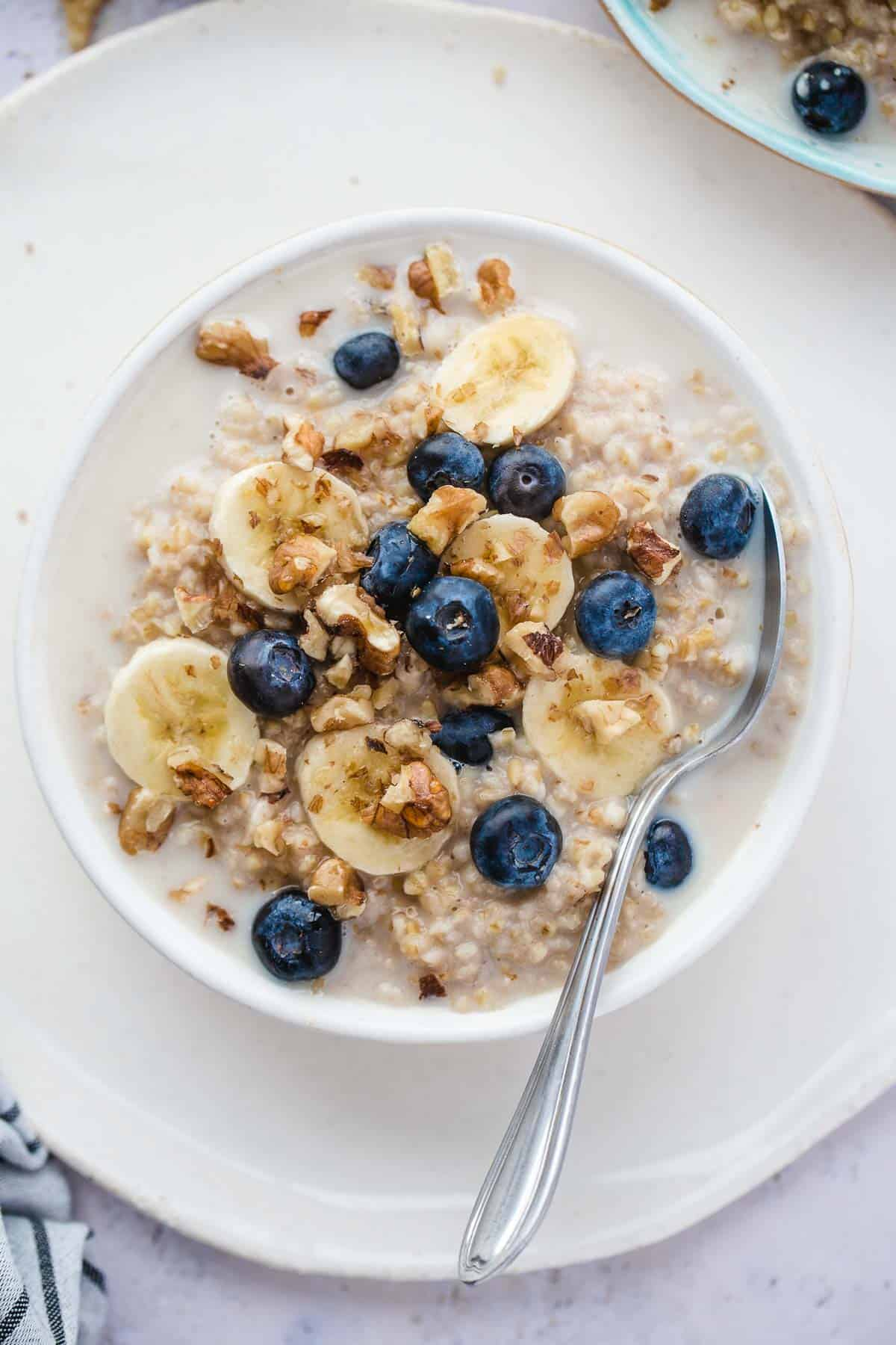 Oatmeal served in a white bowl topped with bananas, blackberries and walnuts