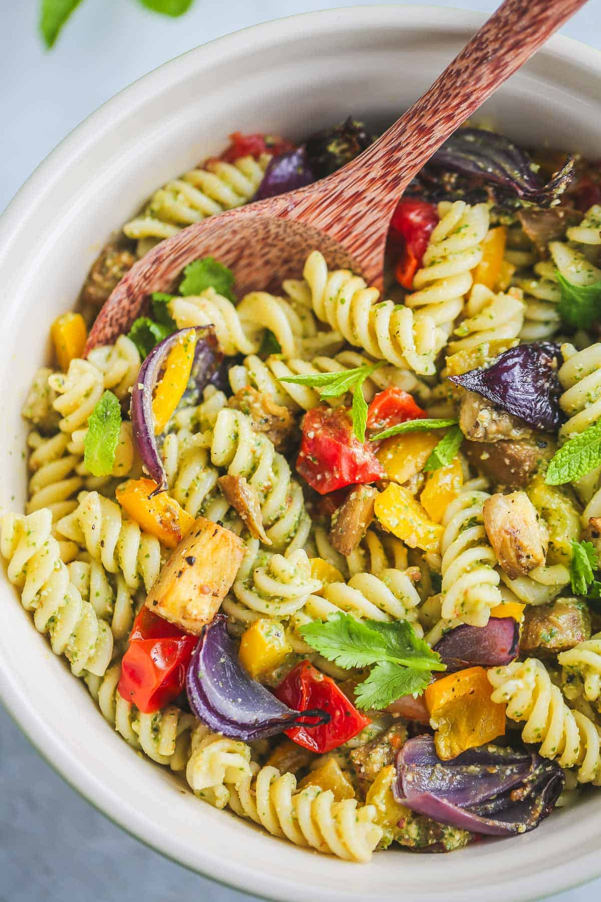 Vegan Pasta Salad served in a bowl, with a serving wooden spoon