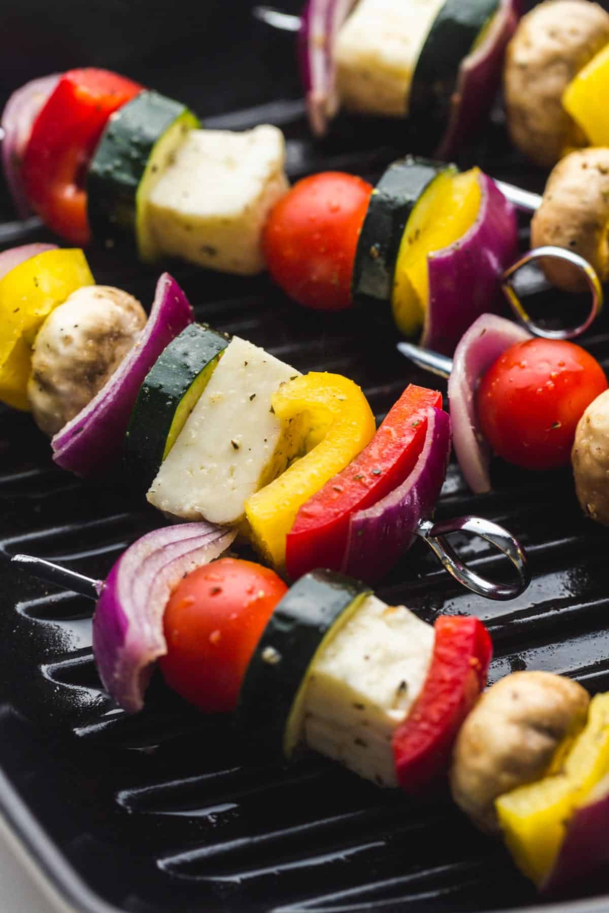 Veggie kabobs on skewers being grilled on a cast iron grill pan