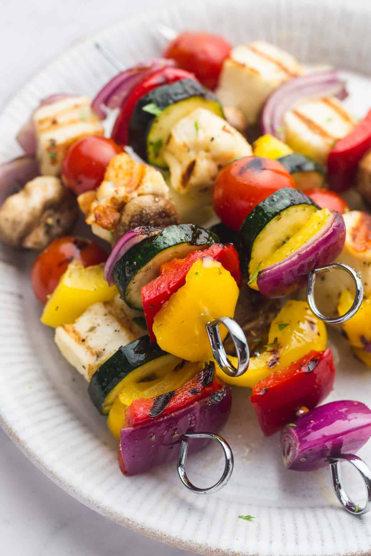Veggie Kabobs with Halloumi on metal skewers on a white plate