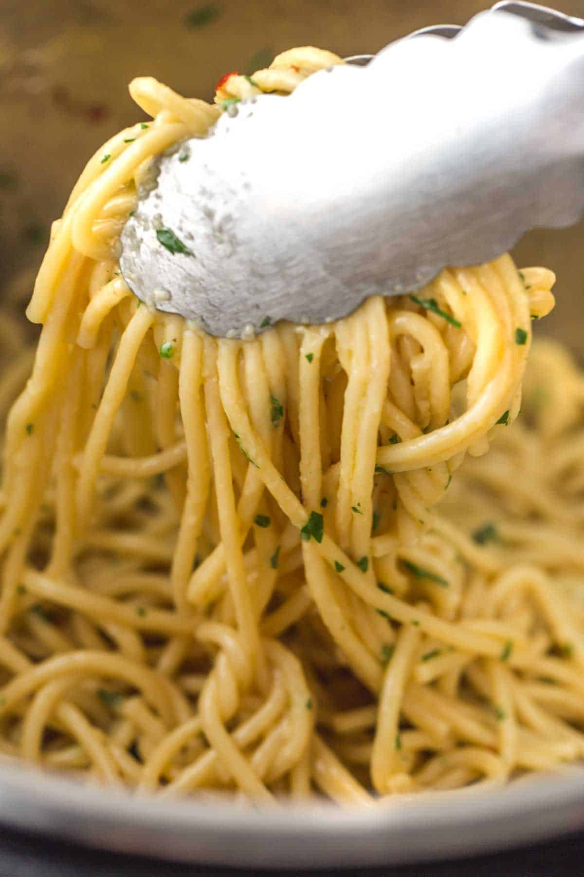 Serving the noodles using kitchen tongs