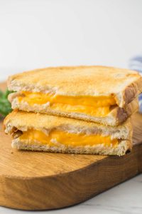 Air Fryer Grilled Cheese sandwich placed on a wooden board