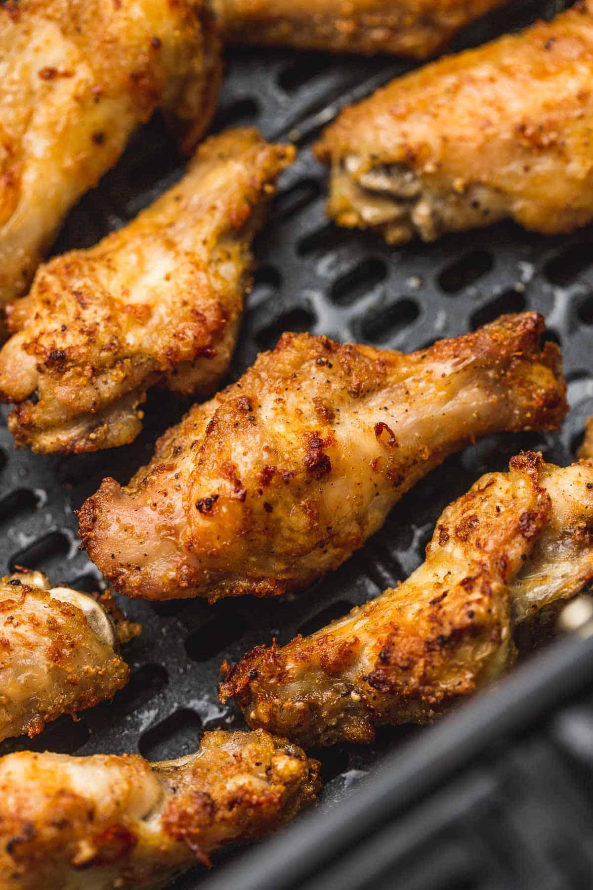 Crispy chicken wings spaced evenly on Air Fryer basket