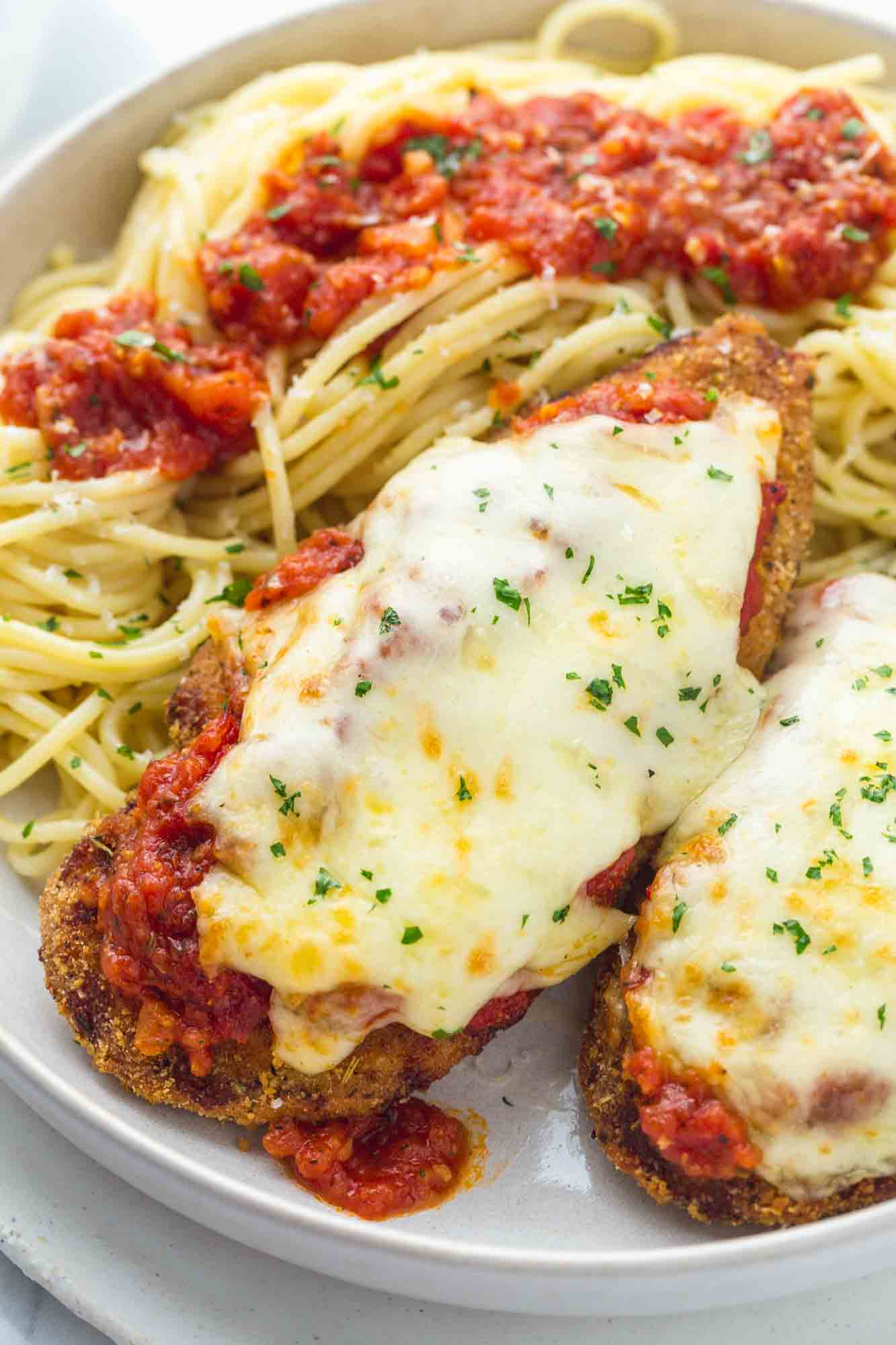 Chicken parmesan served with spaghetti and extra marinara