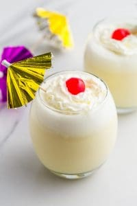 Piña Colada in 2 glasses with whipped cream and maraschino cherries, and cocktail umbrellas