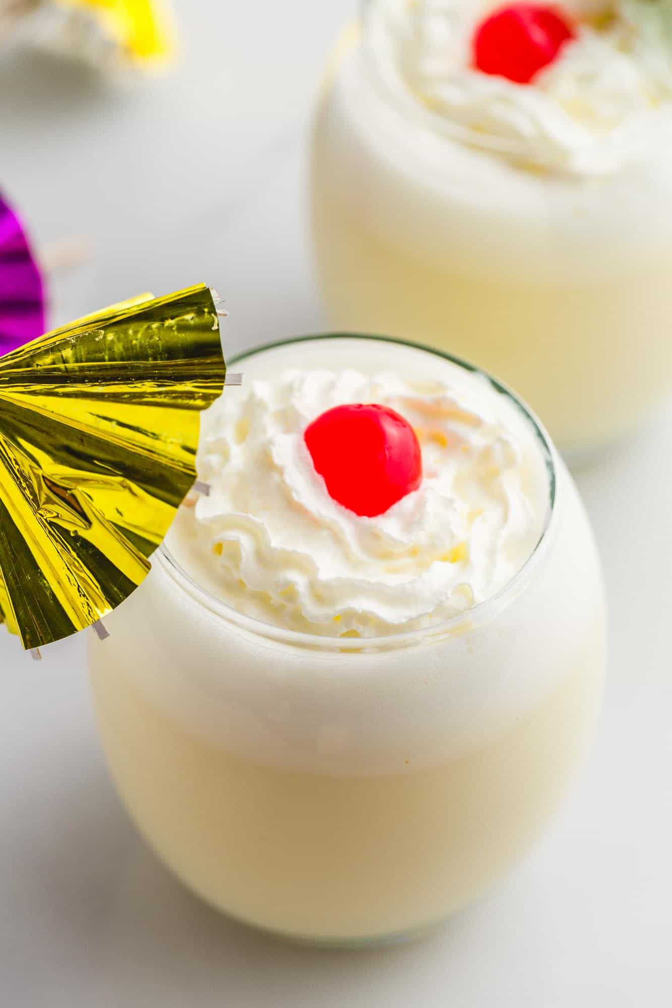 Piña Colada in 2 glasses with whipped cream, maraschino cherries and cocktail umbrellas