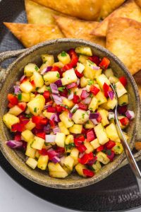 Overhead shot of Pineapple salsa served in a bowl with crispy corn tortilla chips