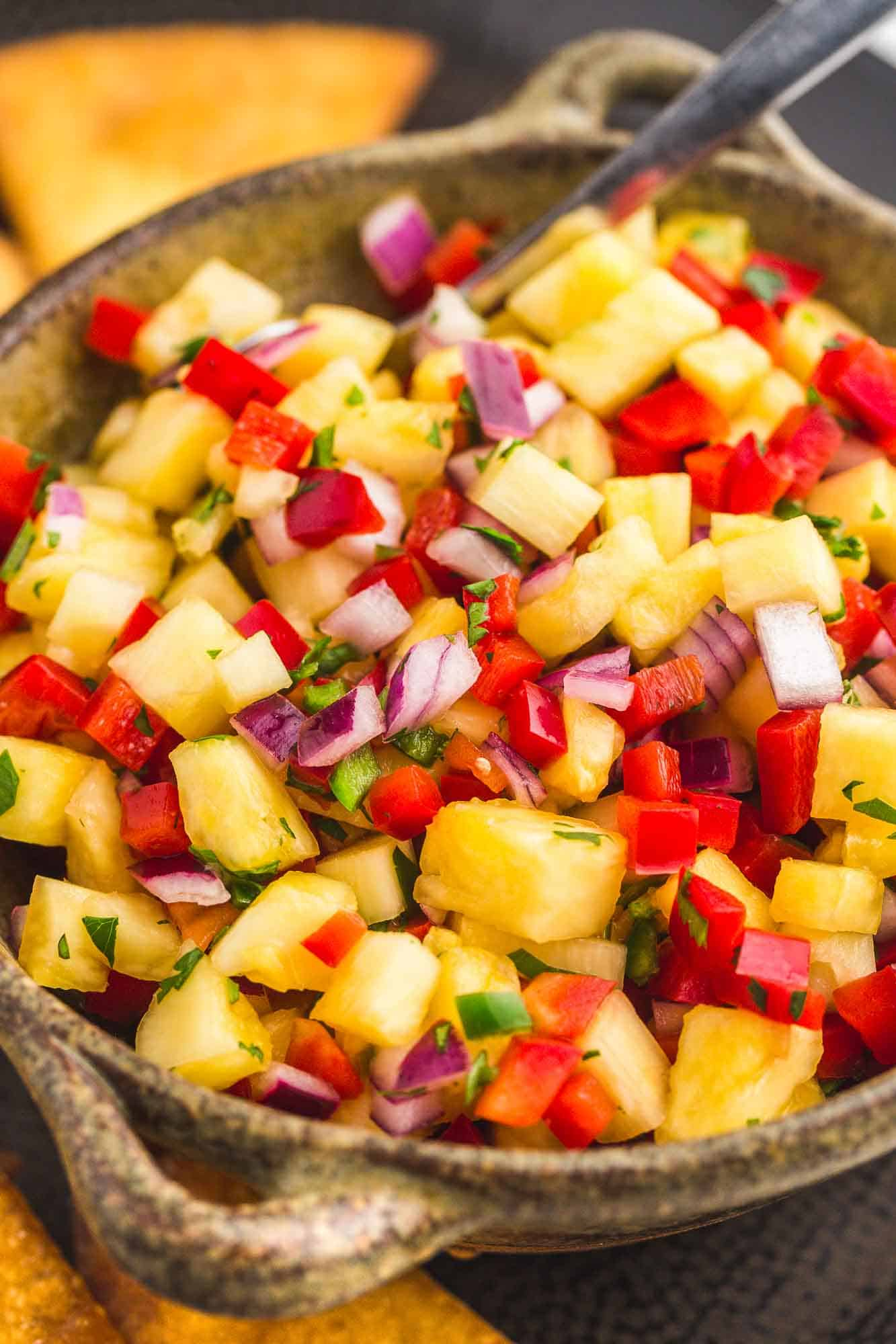 Side shot of a bowl with fresh pineapple salsa and a spoon